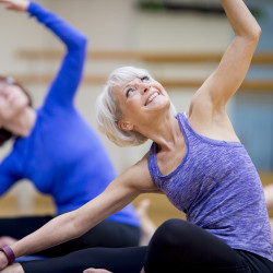 A group of senior adult women are taking a yoga class together at the gym.