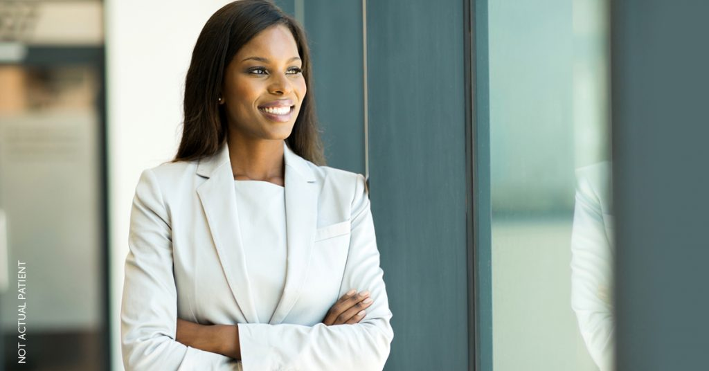 Woman in suit showing off her youthful appearance after having fillers
